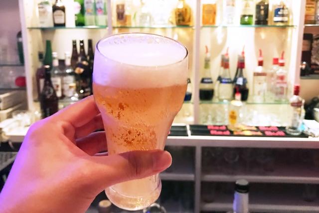 バーでビールグラスを持つ手