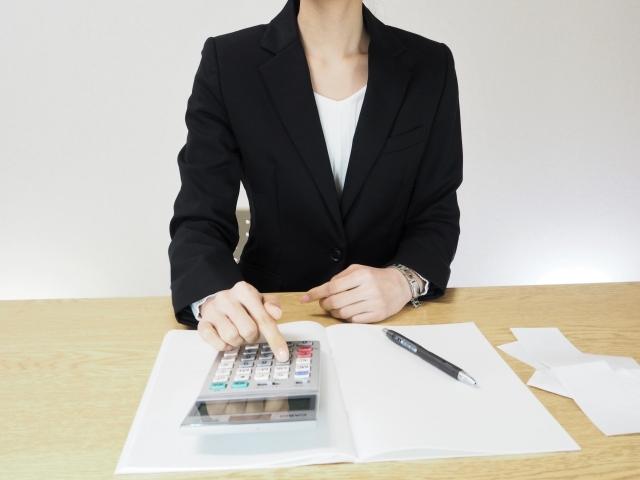 電卓を使用しながら記帳する女性
