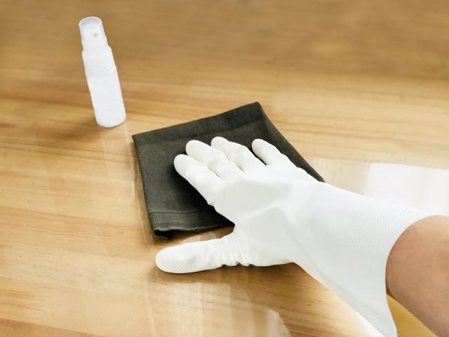手袋をしてテーブルを消毒する手元